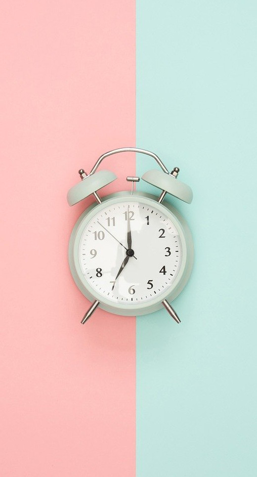 Alarm clock on pink and green background