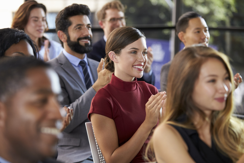 Group of people clapping at a presentation