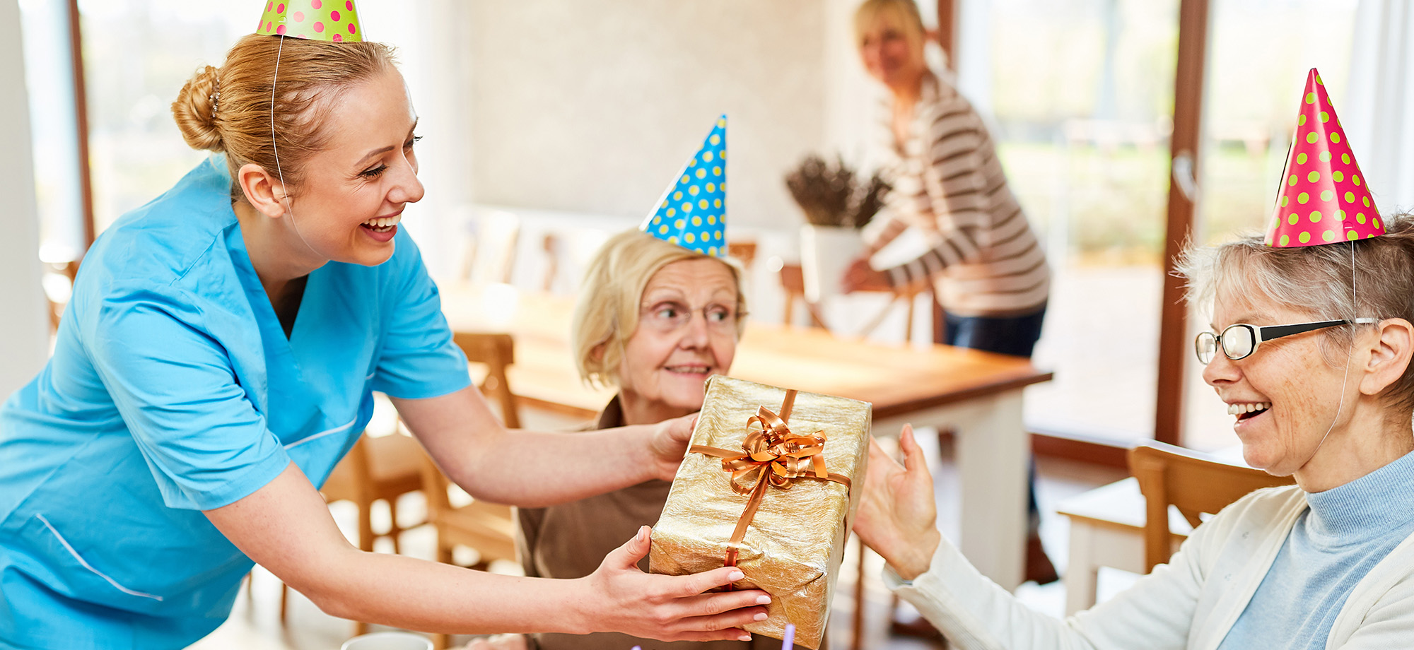 A senior is handed a present by employee at a party