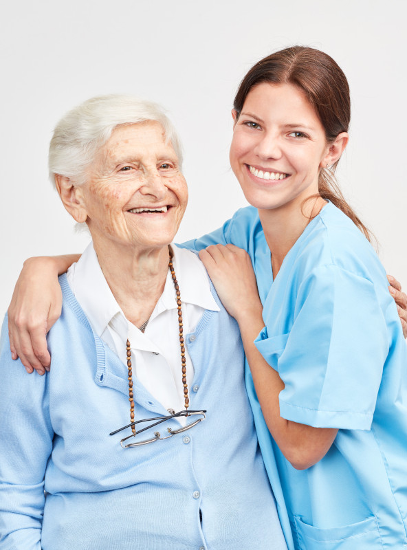 A nurse embraces an elderly woman