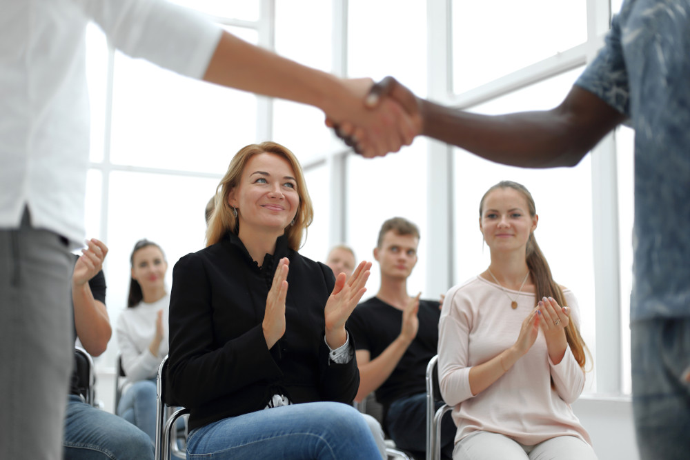 Two people shaking hands in front of a group of seminar participants