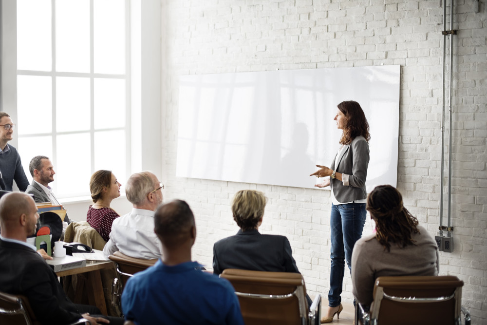 Woman speaks in front of group of people at a seminar