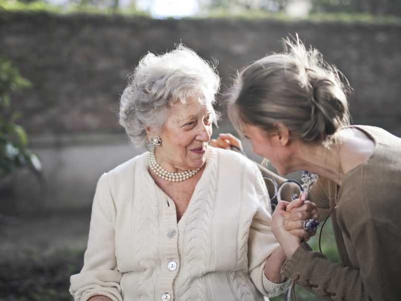 Elderly woman and female companion share a laugh